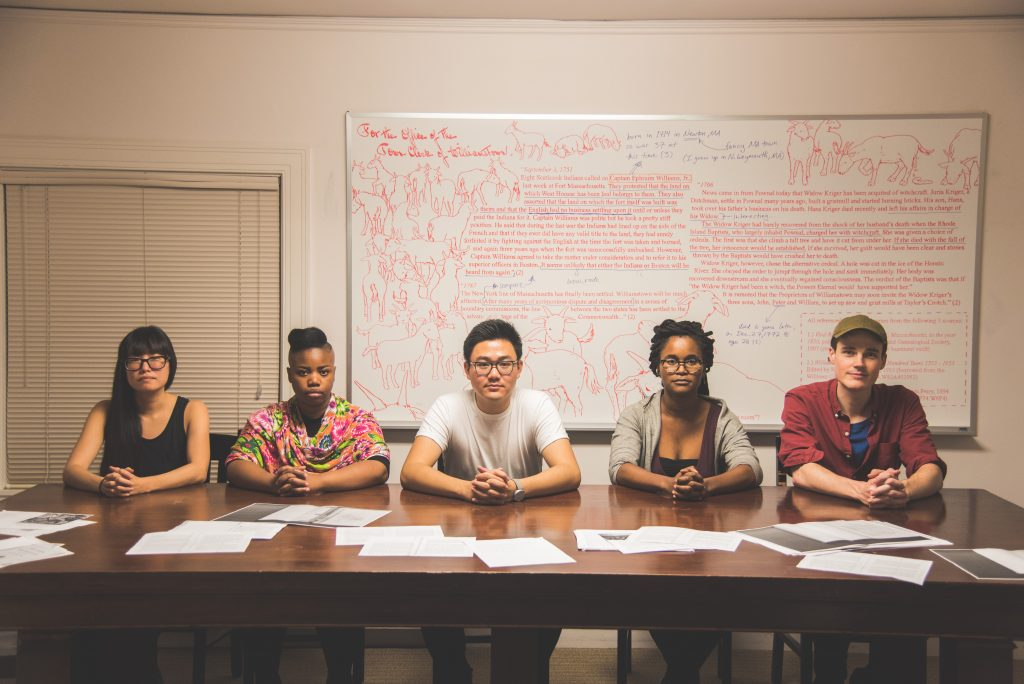 "Photo of Alex Jen, Williams Class of 2018, center, who curated the exhibition ""No Agenda"" in the Williamstown Municipal Building with visiting art professors, from left, Nicole Maloof, Allana Clarke, Ilana Harris-Babou and Zak Arctander. Not pictured is visiting art professor Kim Faler. All five are seated in front of ""For the Office of the Town Clerk of Williamstown,"" 2017. Dry erase marker on white board, 46.5 x 94 in."