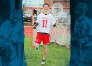 Lacrosse goalie Matt Freitas standing in front of the net holding his lacrosse stick and prosthetic leg.