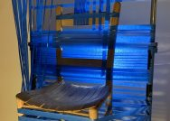 A photo detail of a sculpture made from blue table and a wooden chair.