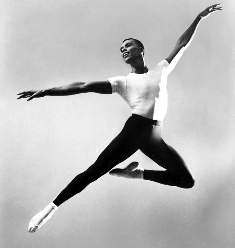 A black and white photo of dancer Arthur Mitchell leaping in mid-air.