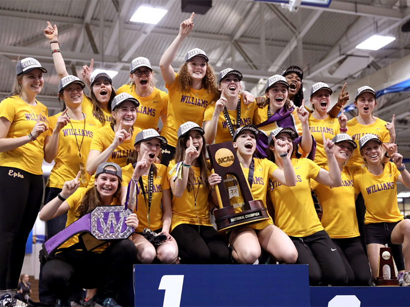 Women's track team posing for a photo with trophy.