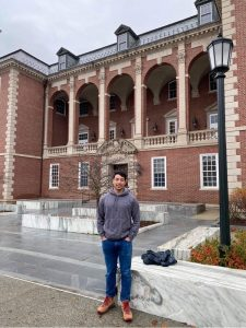 A man in sweatshirt and jeans stands in front of the library at Williams College.