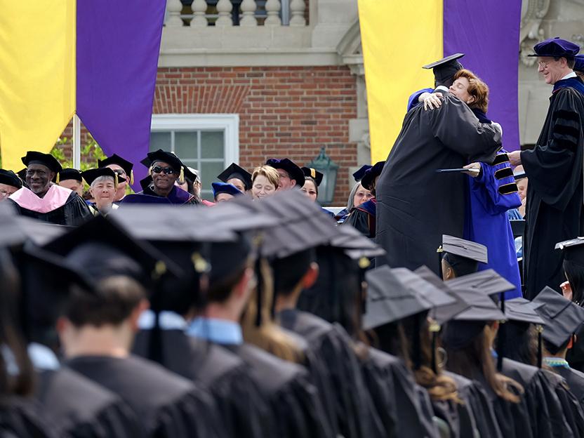 President Mandel hugs a student who graduated.