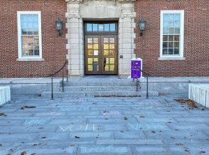 "The word ""vote"" is written in chalk across the walkway in front of Sawyer Library."