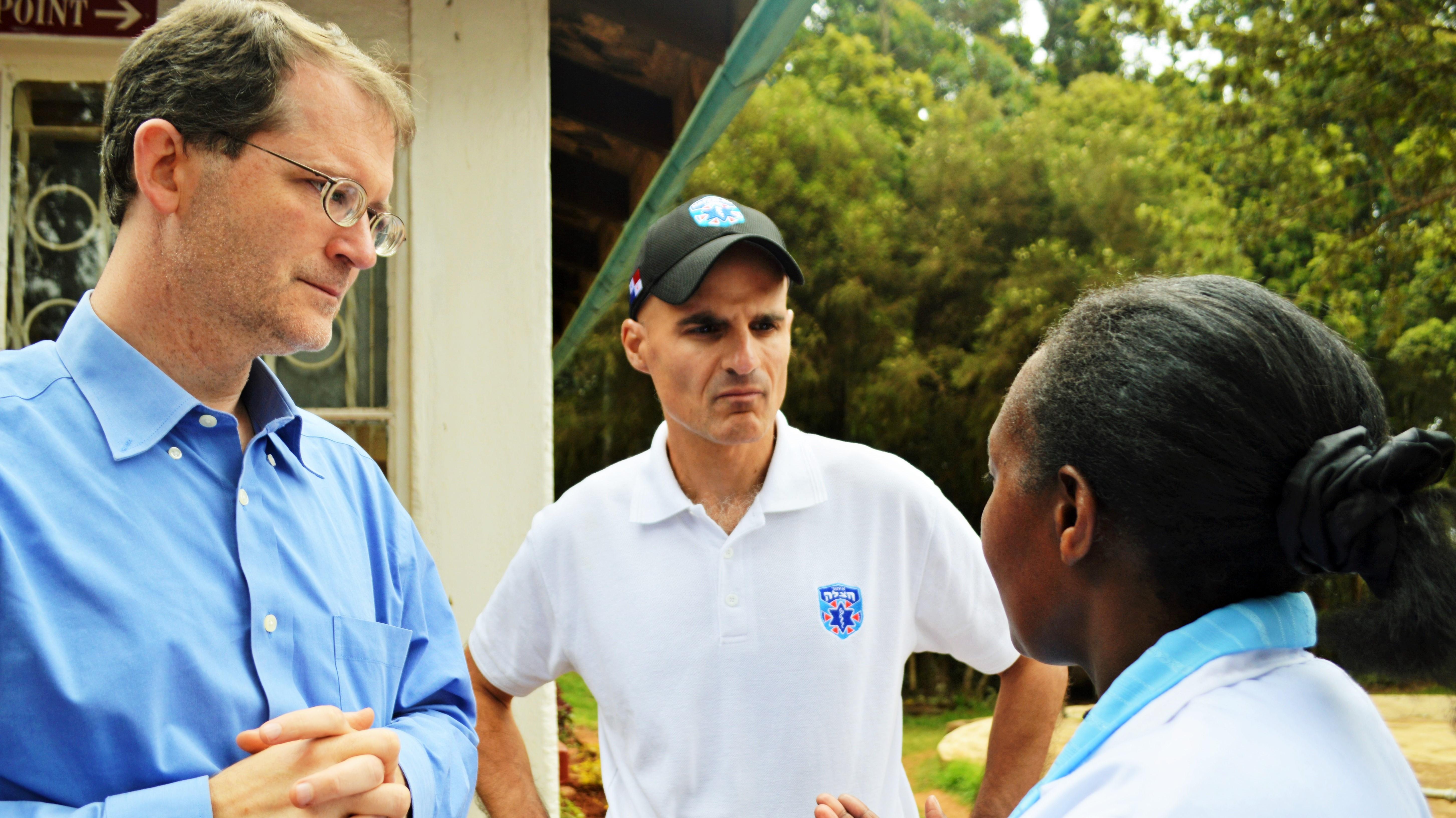 Jon Fielder '94 (left) and Mark Gerson '94 (center) speak with a community worker.