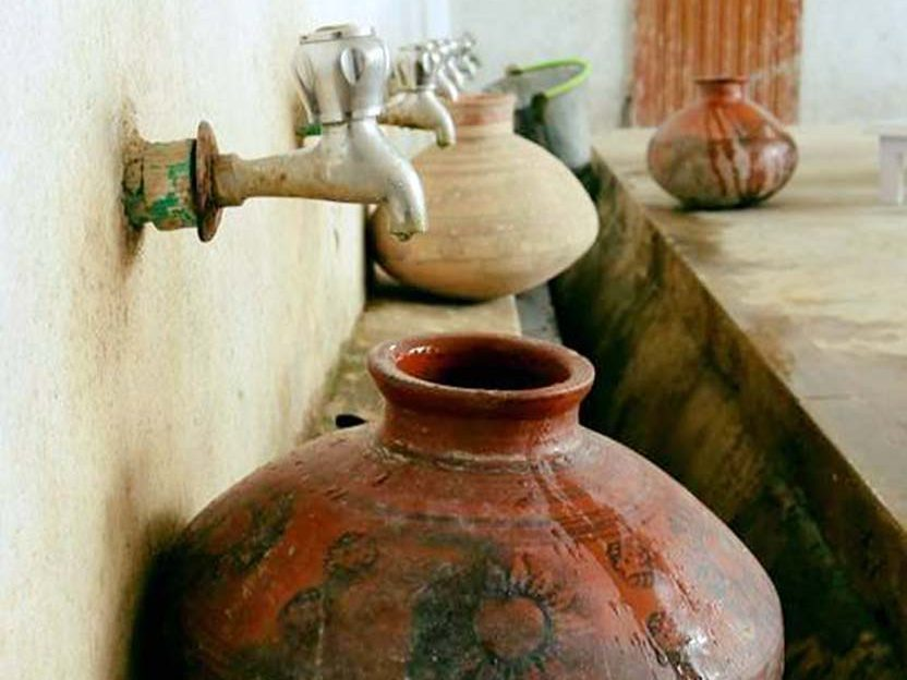 photograph of urns being filled with water supplied by a solar-powered well in rural Pakistan, a project developed by Hamza Farrukh, Williams Class of 2015.