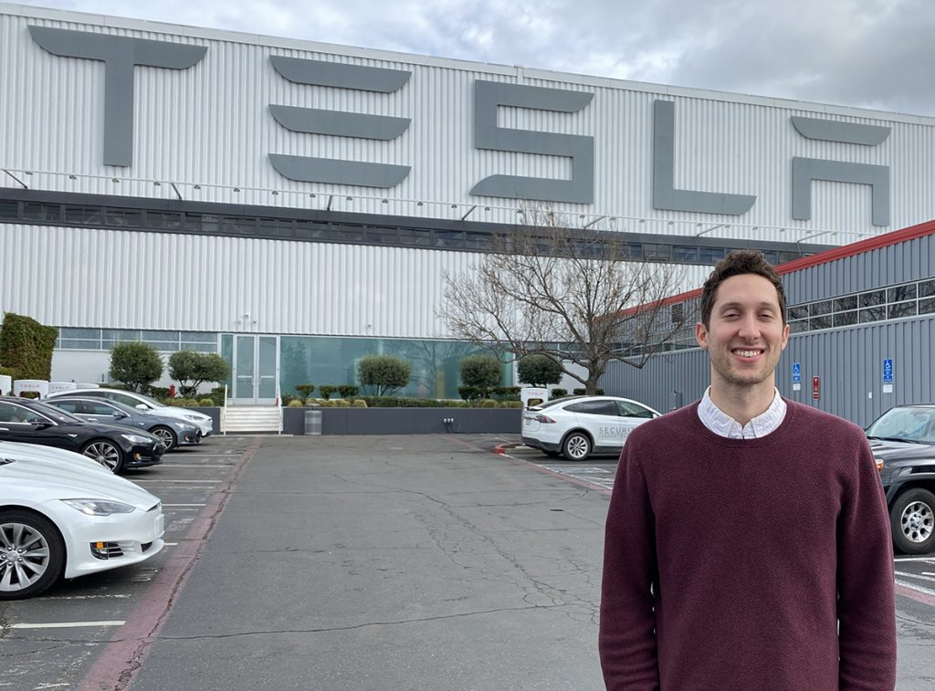 Photo of alumnus Dan Wohl standing outside a Tesla building