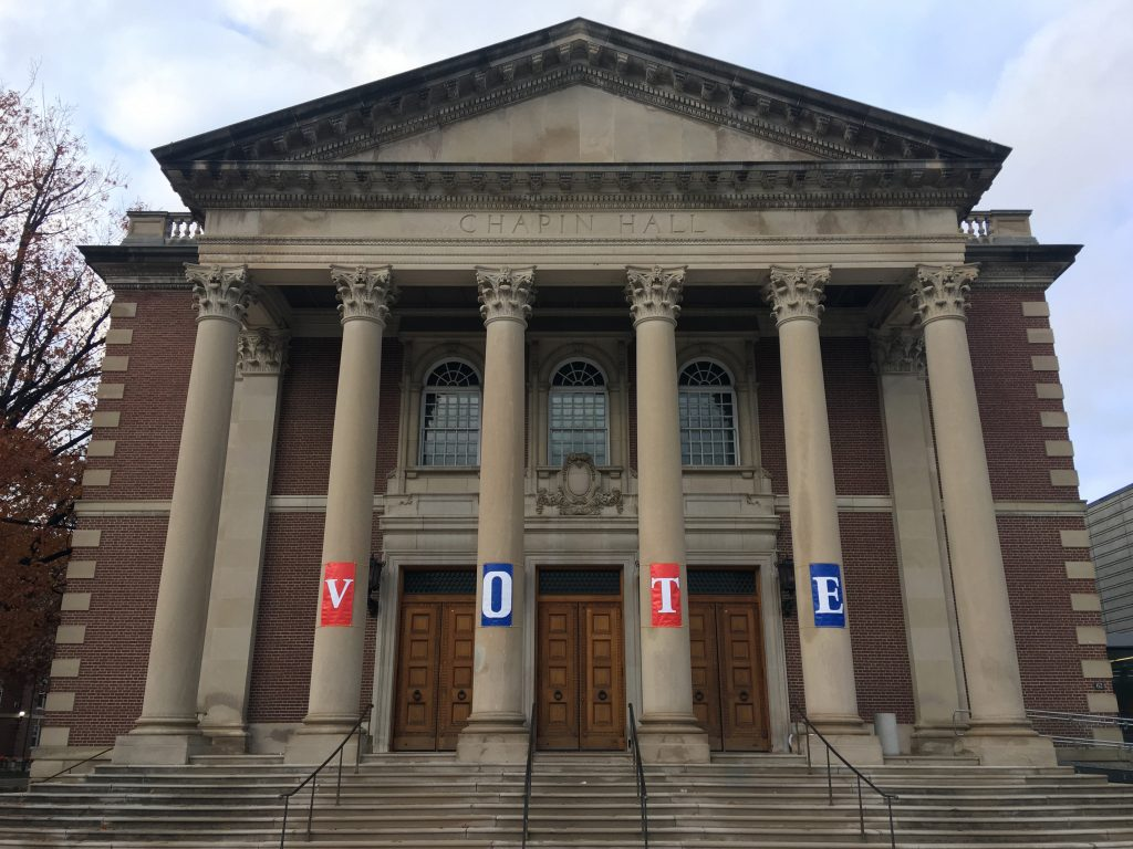 Chapin Hall at Williams College is seen from the front and its columns are decorated with banners spelling out V-O-T-E.