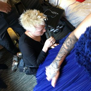 A blond woman kneels on the floor to sew adjustments into a blue dress that a model is wearing.