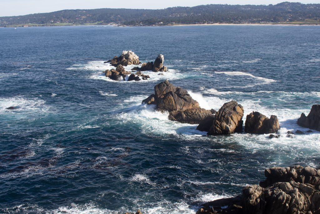 Blue ocean waters are seen swirling around rocks on the coast.