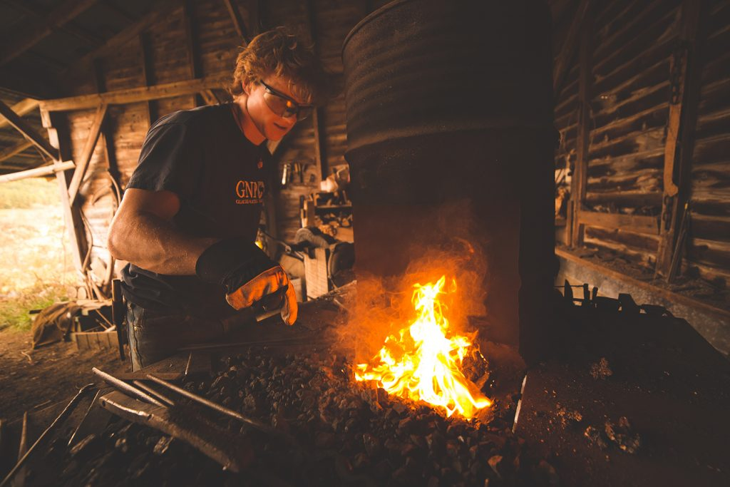 A photo of Jordan Lamothe working near an open fire to create his wares.
