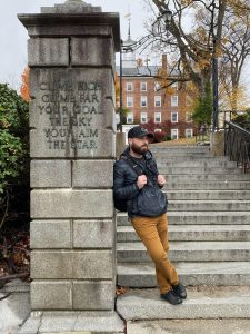 A bearded man in a baseball cap and winter coat leans against a pillar at the bottom of a set of stairs.