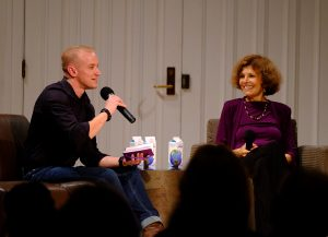 A man and a woman sit on a stage as the man speaks into a microphone.
