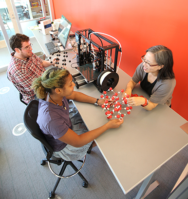 A Williams professor works with two students in a new Center for Educational Technology space.