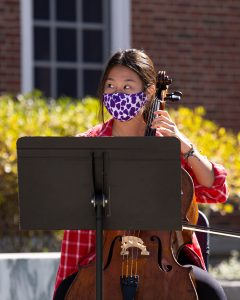 Grace Kim, Class of 2023, performs the cello while wearing a mask in front of the Paresky Center in October.