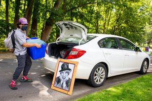 A student wearing a mask unloads a rubber bin from the trunk of his car while a portrait of Harpo leans up against it.