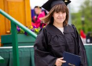 A female student smiles in her cap and gown after just receiving her diploma.