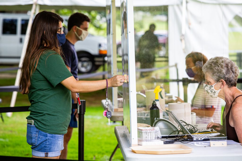 Two students check in to a temporary testing site by holding their I.D.s up to a plexiglass barrier, on the other side of which a volunteer checks them in.