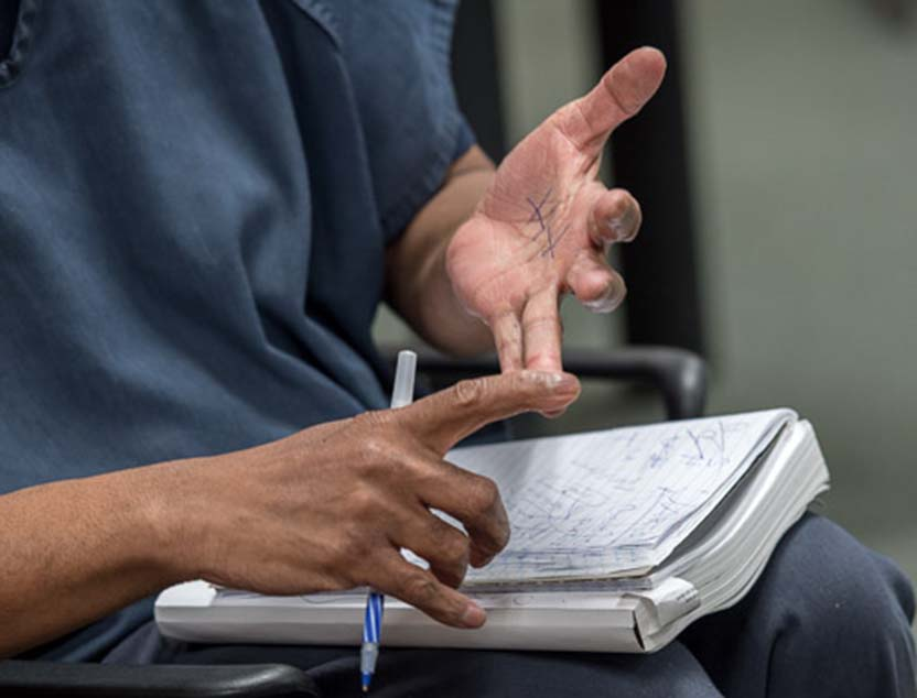 A detail photograph of a student inmate's hands at the Berkshire County House of Corrections, where Williams students are tutoring inmates who are about to be released and are taking a high school equivalency exam called HiSET.
