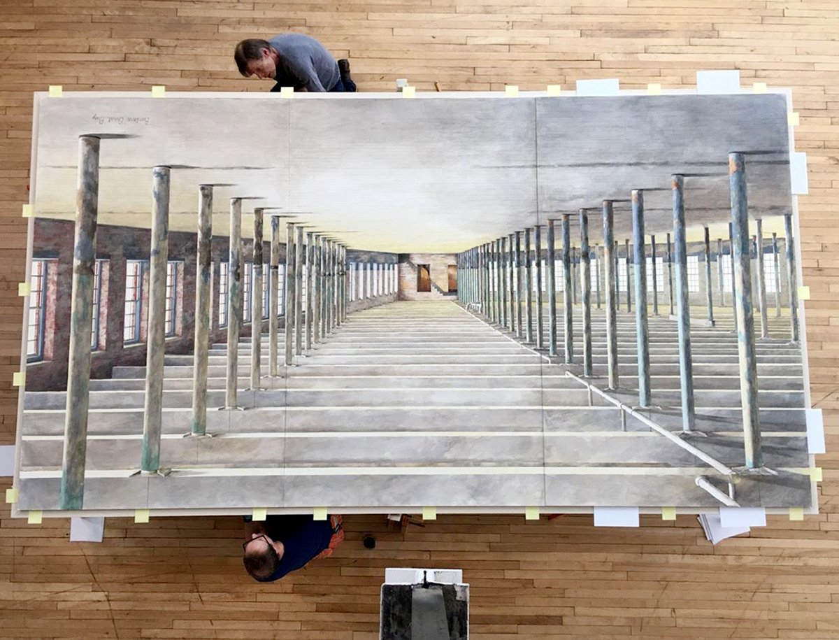 A photograph of workers preparing an oversized water color of the interior of Building 6, the latest expansion of the Massachusetts Museum of Contemporary Art. The water color was painted by Barbara Ernst Prey, Williams Class of 1979.