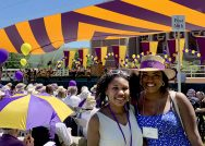 Two alumnae smile at the camera while reunion decorations and crowds are in the background.