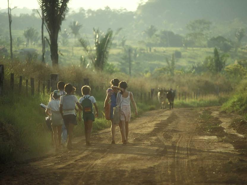Photo of school children walking down dirt road in Brazil