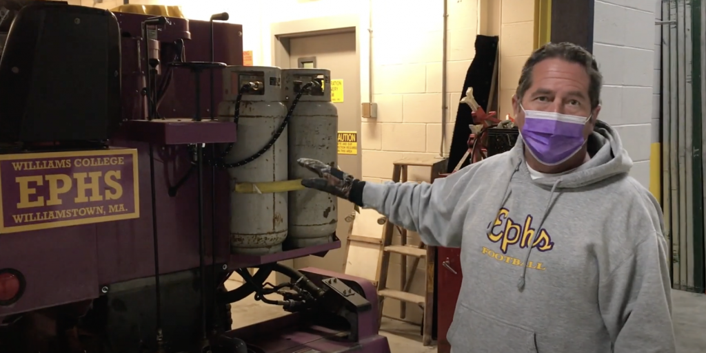 Williams College groundskeeper Jimmy Menard in a purple face mask, pointing to the hockey rink Zamboni.