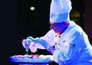 A dining services staff member pipes icing onto a cake during a February performance of