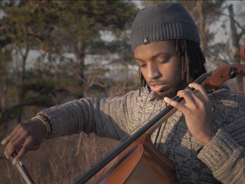 Tasan Smith-Gandy playing his cello outdoors.