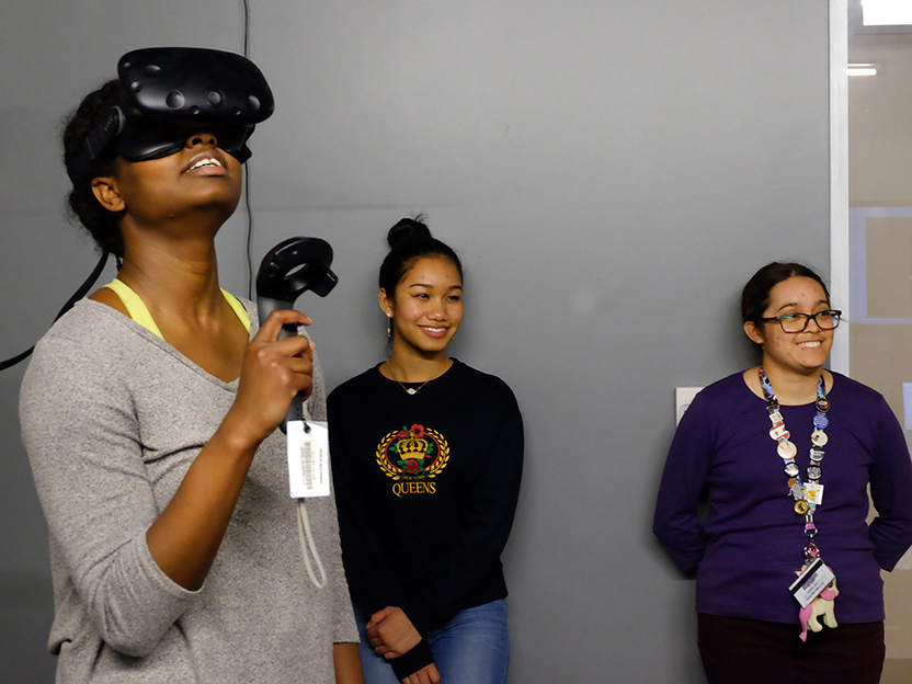 A photo of students in Professor Christorpher Goh's Introductory Chemistry course using virtual reality to learn about molecules. The student in the foreground wears black goggles and is looking up at the ceiling.