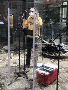 Student singing in an outdoor recording studio.