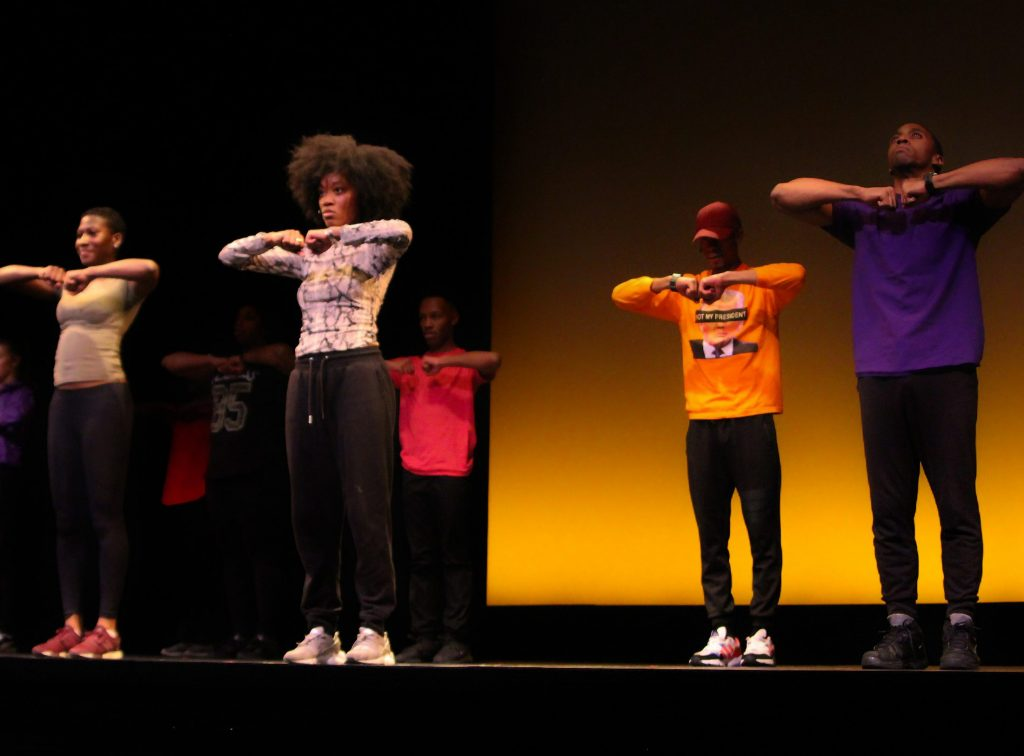 A group of men and women perform a step routine on stage.