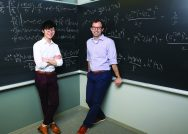Photograph of William Chen, Williams Class of 2019, on the left and Williams Economics Professor Greg Phelan, both standing in front of a chalk board with economic equations written all over it.