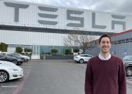 Photo of alumnus Dan Wohl standing outside a Tesla building
