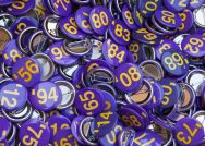 A basket full of purple and gold buttons with graduation years on them.