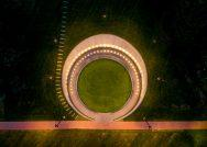 An aerial view of the Memorial to Enslaved Laborers at the University of Virginia shows a circular brick wall lined by lights all around, with a grassy lawn in the middle.